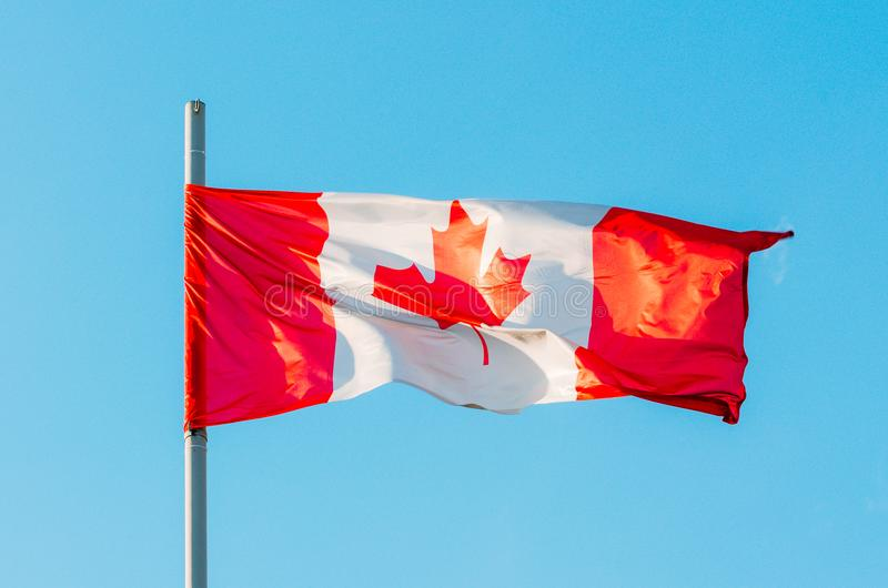 Wellenartig bewegende bunte Kanada-Flagge auf blauem Himmel lizenzfreies stockfoto