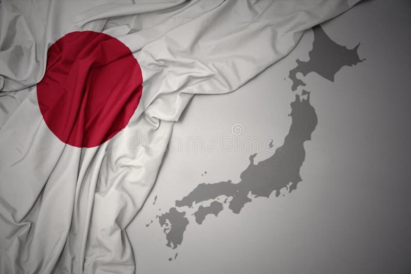 Wellenartig bewegende bunte Staatsflagge und Karte von Japan stockfotos