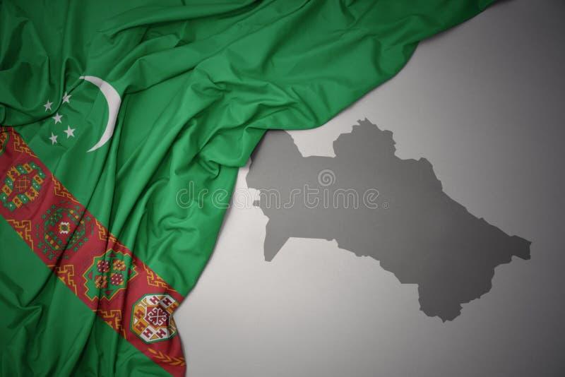 Wellenartig bewegende bunte Staatsflagge und Karte von Turkmenistan lizenzfreies stockbild