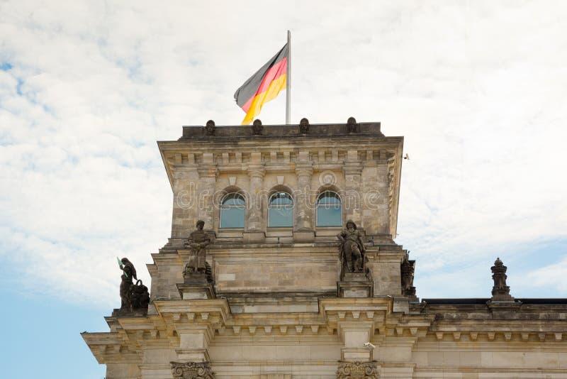Wellenartig bewegende deutsche Flagge über dem Reichstag-Gebäude in Berlin stockbilder