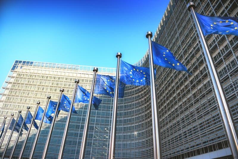 Wellenartig bewegende EU-Flaggen vor Europäischer Kommission in Brüssel stockbilder