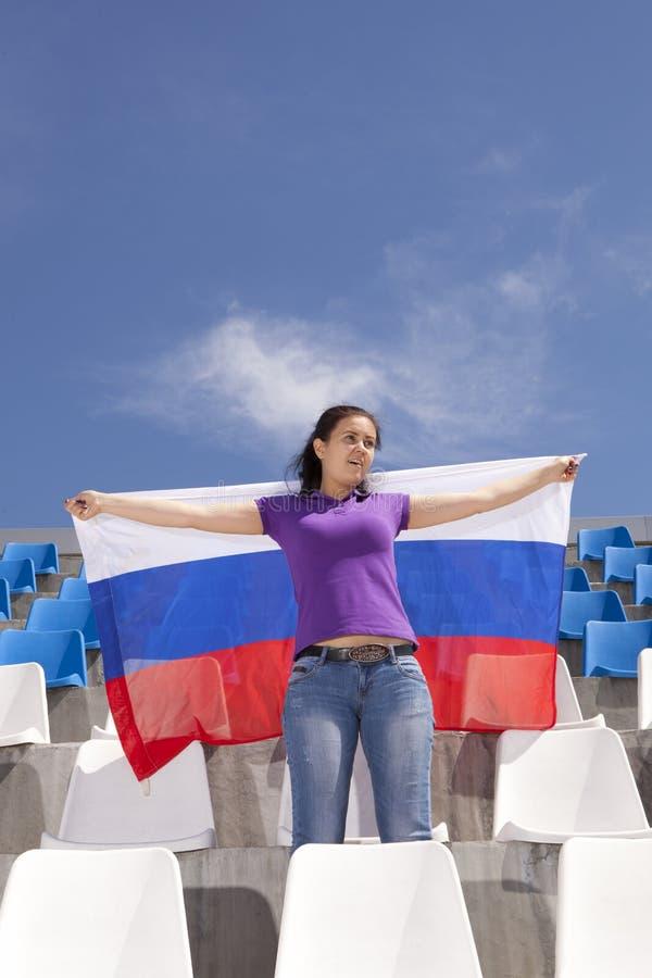 Wellenartig bewegende Flagge des Mädchensportfans stockfotos