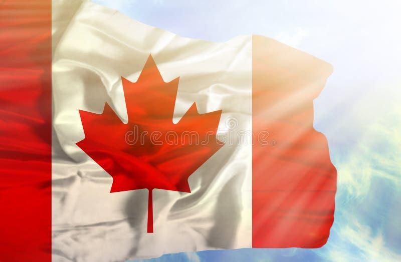 Wellenartig bewegende Flagge Kanadas gegen blauen Himmel mit Sonnenstrahlen stockfoto