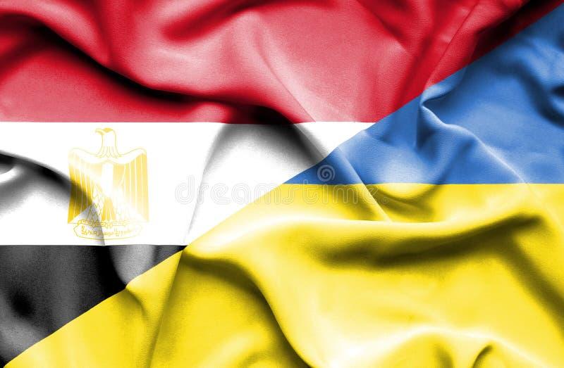 Wellenartig bewegende Flagge von Ukraine und von Ägypten lizenzfreie stockfotos
