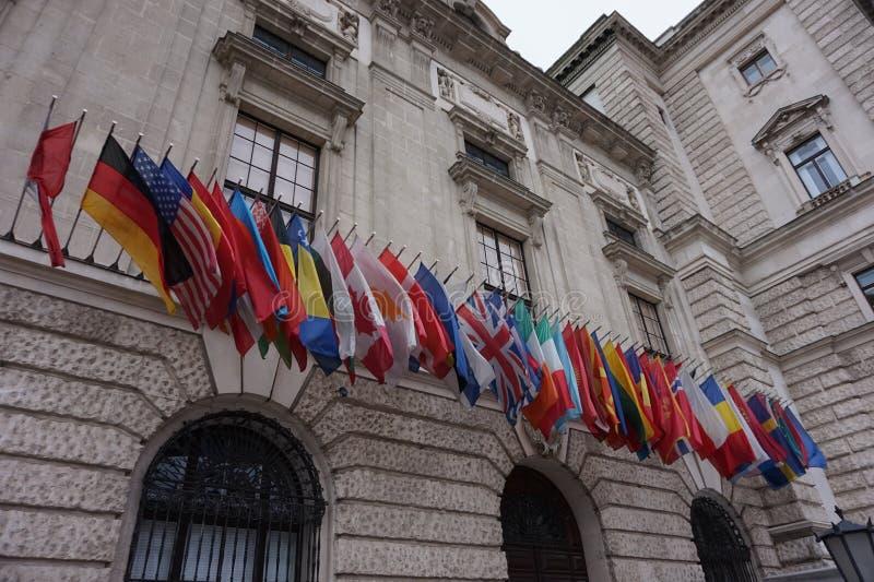 Wellenartig bewegende Flaggen der Europäischen Gemeinschaft am Hofburg-Palast in Wien stockbilder
