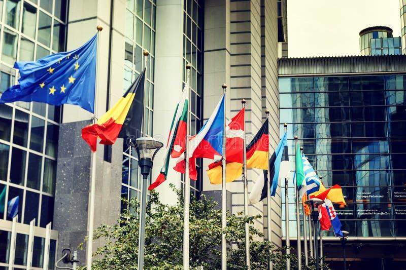 Wellenartig bewegende Flaggen vor Gebäude des Europäischen Parlaments in Brüssel lizenzfreies stockbild