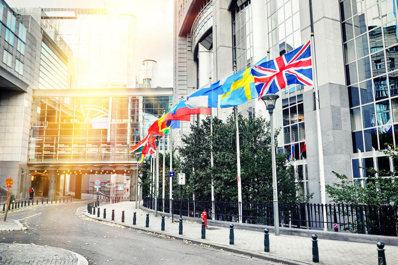Wellenartig bewegende Flaggen vor Gebäude des Europäischen Parlaments Brüssel, stockbild