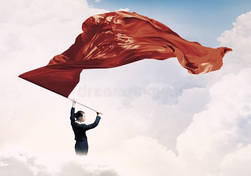 Wellenartig bewegende rote Fahne der Frau Gemischte Medien lizenzfreie stockfotografie