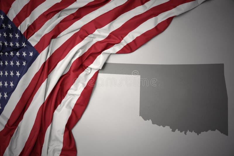 Wellenartig bewegende Staatsflagge von Staaten von Amerika auf einem grauen Oklahoma geben Kartenhintergrund an lizenzfreies stockbild