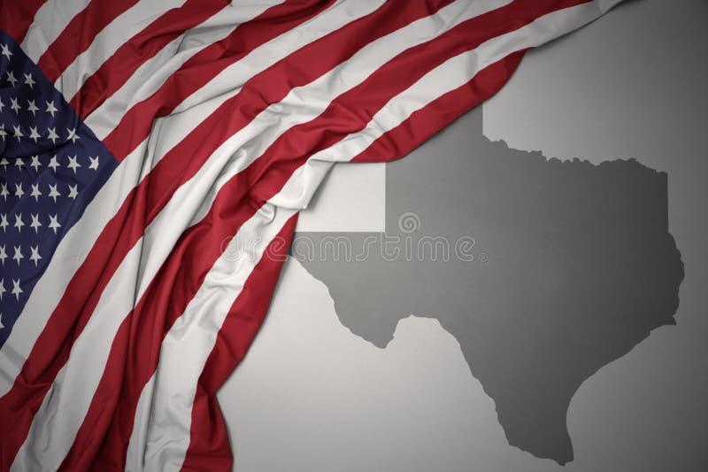 Wellenartig bewegende Staatsflagge von Staaten von Amerika auf einem grauen Texas geben Kartenhintergrund an stockfotografie