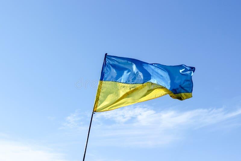Wellenartig bewegende ukrainische gelb-blaue Flagge gegen einen blauen Himmel stockbild