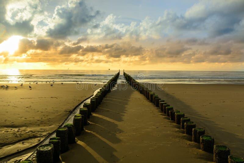 Wellenbrecher auf dem Strand bei Sonnenuntergang in Domburg Holland lizenzfreie stockbilder