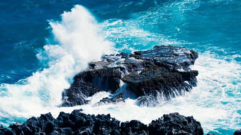 Wellenbrecher auf einem Felsen von einer Vulkaninsel lizenzfreie stockfotografie