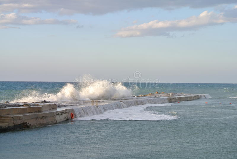 Wellenbrecher gegen Seeelemente lizenzfreies stockbild