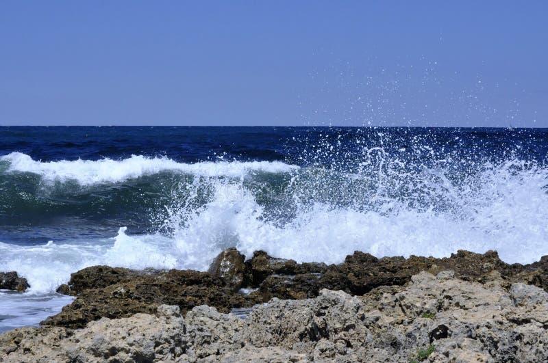 Wellenbruch gegen Felsen stockfotografie