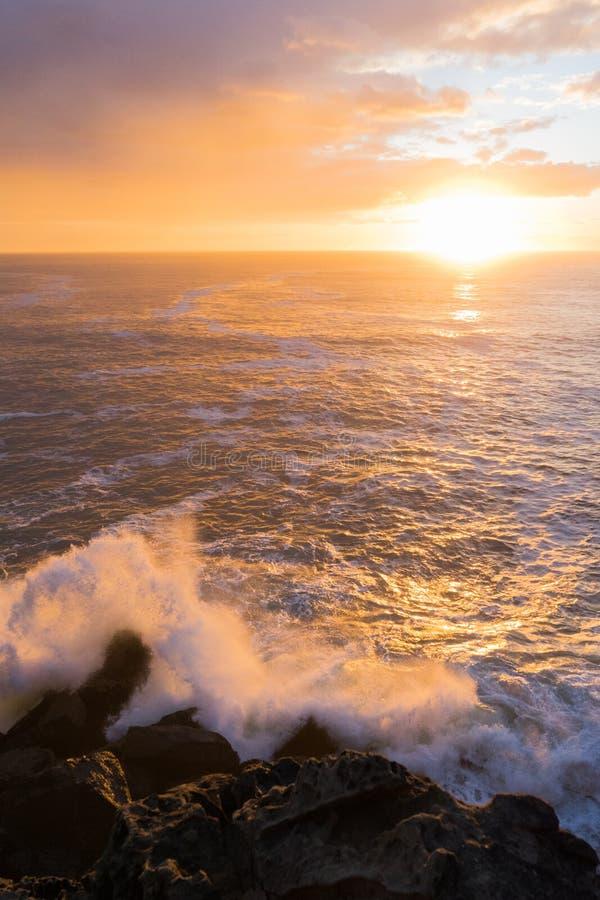Wellenspritzen und -sonnenuntergang stockfoto