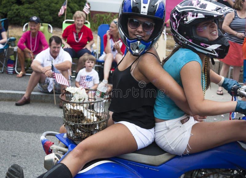 Wellfleet, Massachusetts, USA 4. Juli 2014: Zwei junge Frauen, die auf ein Motorrad im Wellfleet fahren stockbilder