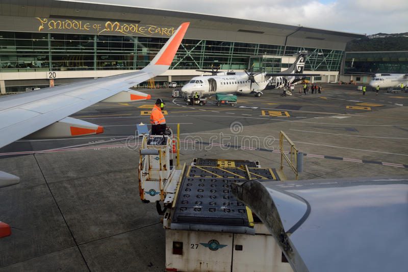 Wellington airport. WELLINGTON, NEW ZEALAND, OCTOBER 19, 2016: Ground staff check a Jetstar plane and an Air New Zealand jet on the tarmac at Wellington Airport stock image