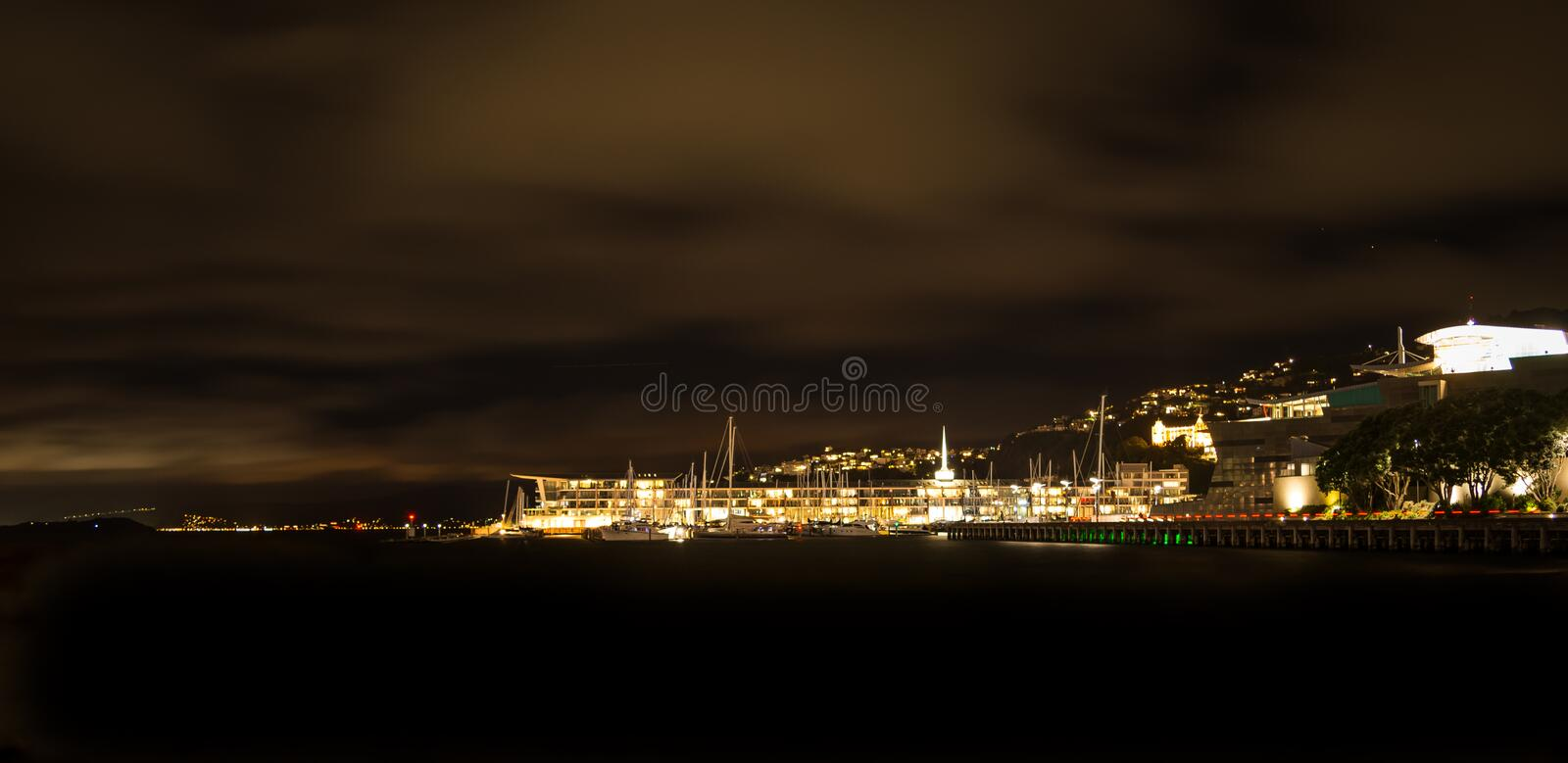 Wellington city waterfront at night: Lit-up houses on the slopes of Mt Victoria and street lights shining over calm royalty free stock image