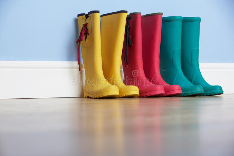 Wellingtons lines up against wall stock photos