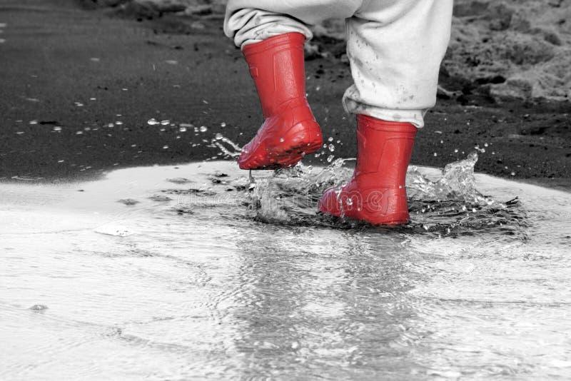 Wellingtons na poça botas de borracha da criança no fundo do mar foto de stock