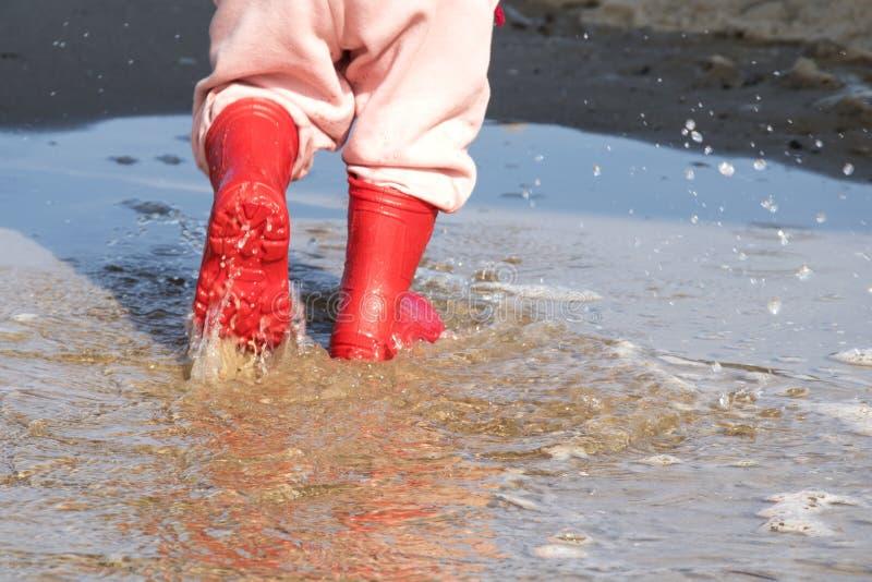 Wellingtons na poça botas de borracha da criança no fundo do mar fotos de stock royalty free