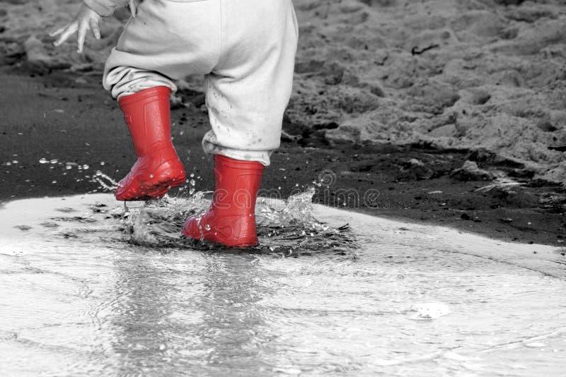 Wellingtons na poça botas de borracha da criança no fundo do mar fotos de stock