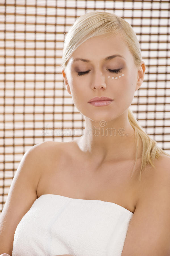 In a wellness. Beauty advertising shot of a blond girl in act to be in a wellness farm with towel and cosmetic product royalty free stock images