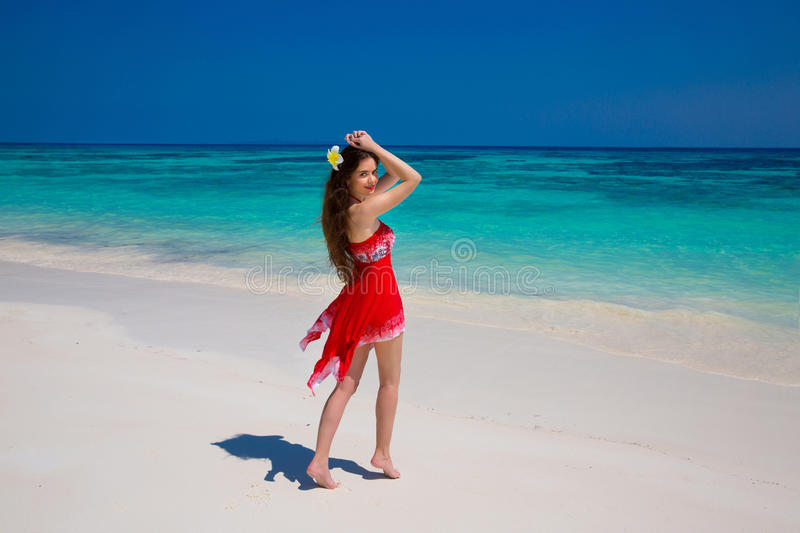 Wellness. Beautiful woman smiling on the beach. Young female in. Red dress enjoying sunny day on tropical beach, summer vacation. Travel royalty free stock image
