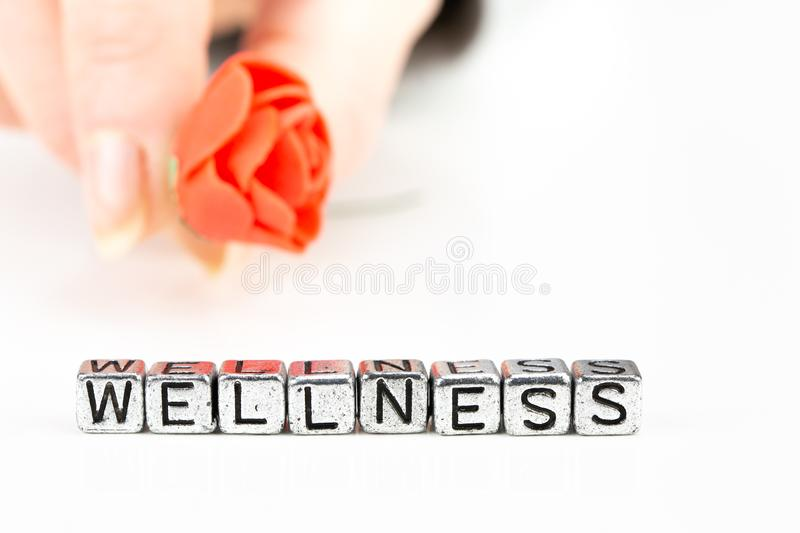 Wellness concept with cube letters and a woman hand holding a rose royalty free stock photos