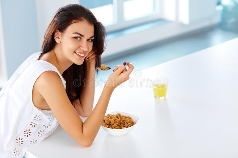 Wellness concept. Woman having breakfast and smiling. Healthy ea. Wellness concept. Beautiful young woman having breakfast and smiling. Healthy eating royalty free stock photo
