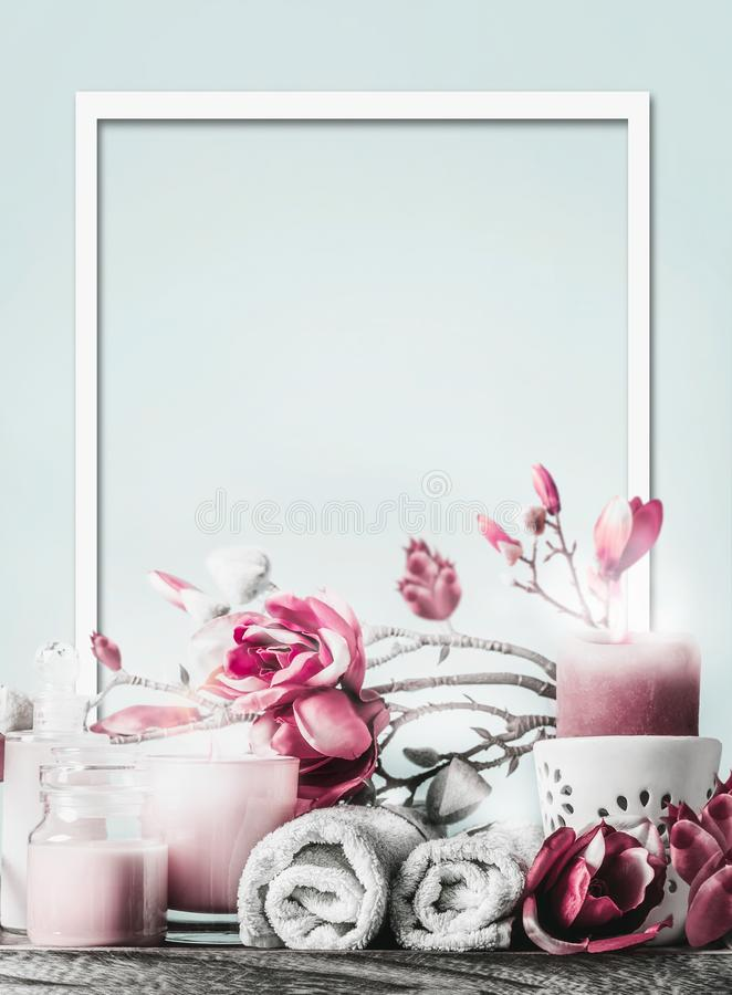 Wellness frame with body care cosmetic products, candles, flowers and towels at light blue background with copy space. Healthy. Still life. Spa layout royalty free stock photography