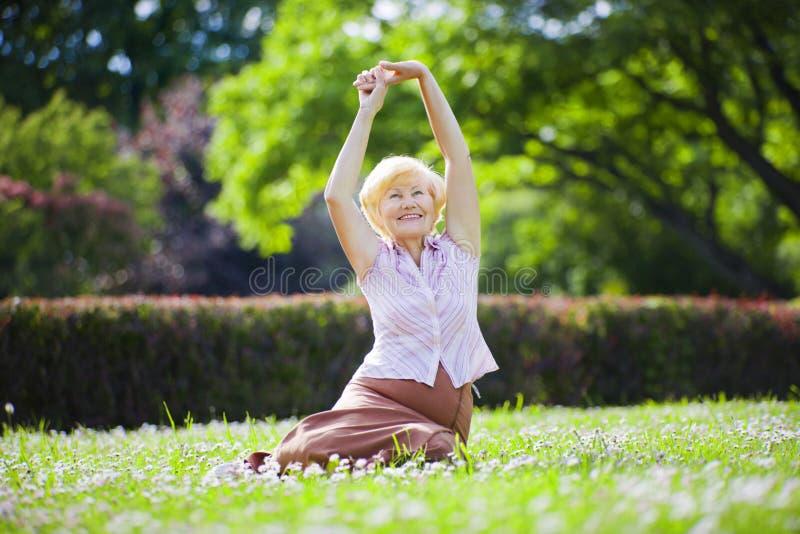 Wellness. Mentala hälsor. Optimistisk gammal kvinna som övar i öppen luft royaltyfri bild