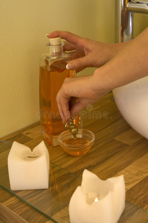 Wellness oil. Woman hands filling up natural massage oil inside a wellness room royalty free stock photo