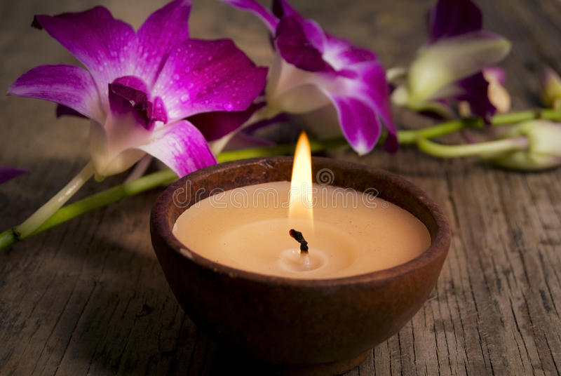Wellness in old style. A beautiful pink orchid with candle on old wood table like a concept of wellness and beauty in old style stock image
