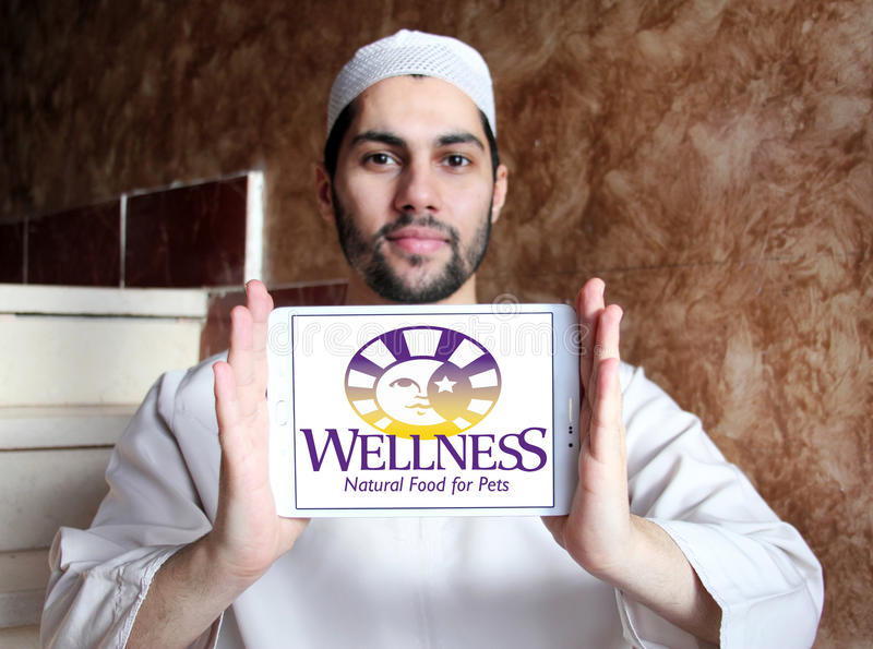 Wellness pet food logo. Logo of wellness pet food company on samsung tablet holded by arab muslim man royalty free stock photo