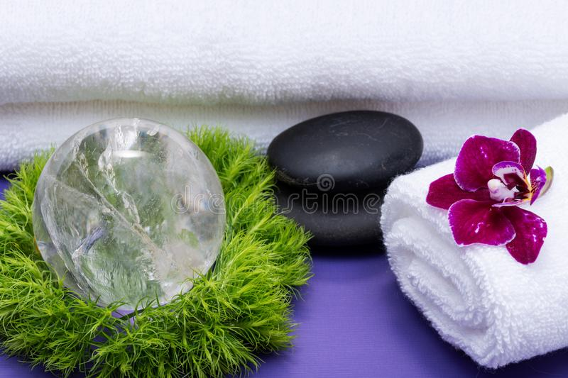 Wellness Relax concept with Spa elements. Rolled White Towels, Basalt Stones, Orchid, Clear Quartz Sphere and Dianthus Flowers. On purple background stock photos