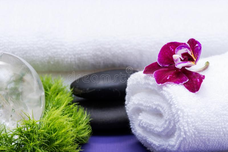 Wellness Relax concept with Spa elements. Rolled White Towels, Basalt Stones, Orchid, Clear Quartz Sphere and Dianthus Flowers. On purple background stock images