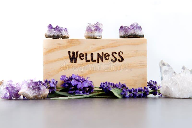 Wellness - słowo palący w drewnie z purpurowymi lawenda kwiatami, ametystem i kwarcowymi kryształami na łupku z białym tłem, obrazy royalty free