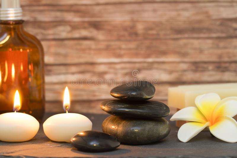 Wellness and spa composition candles with massage stones. Wellness and spa composition with candles, stacked massage stones and oil stock image