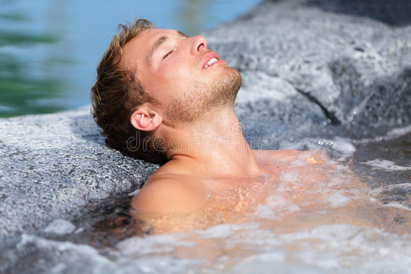 Wellness Spa - man relaxing in hot tub whirlpool. Jacuzzi outdoor at luxury resort spa retreat. Handsome young male model relaxed with eyes closed resting in stock image