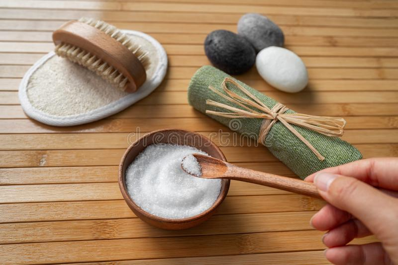 Wellness spa products woman holding bath epsom salts in natural wooden bowl for foot scrub skin body heatlh care. Scrubbing loofah royalty free stock photos
