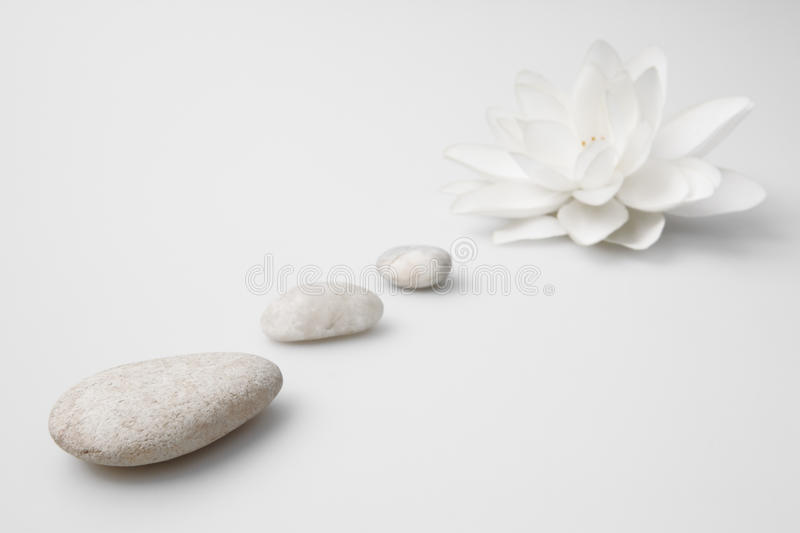 Wellness still life pebbles and white lily. High key studio shot royalty free stock images