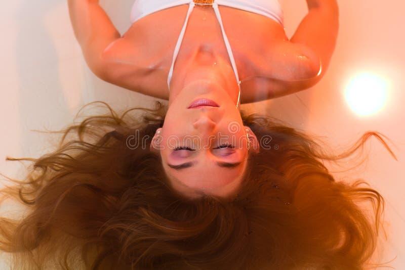 Wellness - ung kvinna som flottörhus i Spa arkivbild