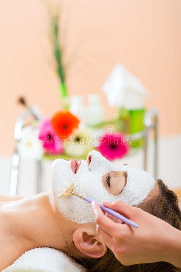 Wellness - woman getting face mask in spa. Wellness - woman receiving nurturing facial mask in spa for moist and clean skin royalty free stock photos