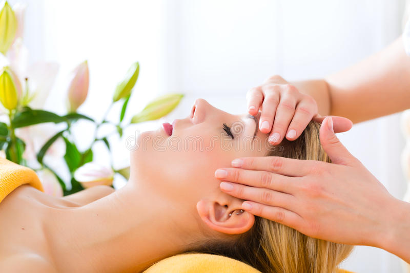 Wellness - woman getting head massage in Spa stock photography