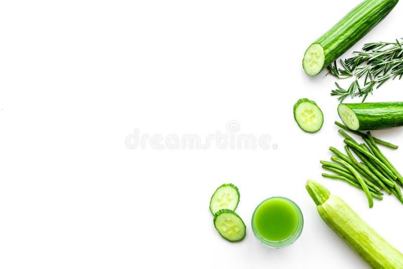 Wellnessbeståndsdelar Den gröna detoxen dricker med gurkan, sparris och grönska på vit copyspace för den bästa sikten för bakgrun royaltyfri fotografi