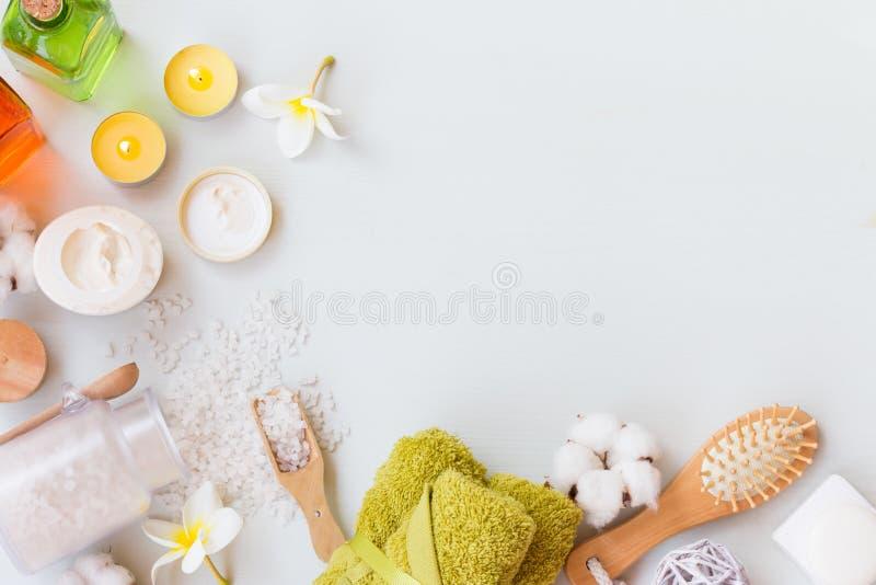 Wellnessbrunnsortinställning med naturliga tvål, kräm, stearinljus och handdukar på en vit träbakgrund med kopieringsutrymme arkivbilder