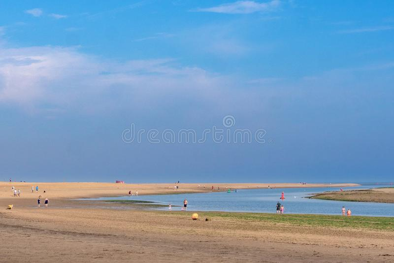 Wells next the Sea Beach. Early risers on Wells beach, no crowds at this time on a Sunday. Wells next the Sea Norfolk. Taken at low tide in high summer. Image of stock photos