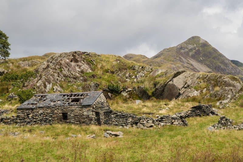 Welse berg Cnicht met ruïne van steenplattelandshuisje in voorgrond stock foto's